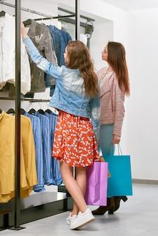 Foto de amigos comprando ropa en la tienda.