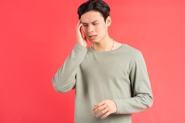 Una foto de un apuesto hombre asiático frotándose la cabeza con la mano debido a su migraña