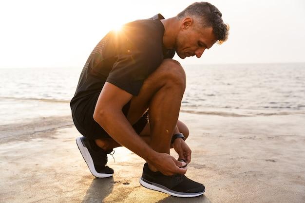 Foto de apuesto hombre caucásico de 30 años en chándal y zapatillas de deporte en cuclillas en el muelle junto al mar y atarse los zapatos