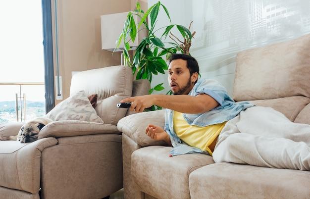 Foto de un apuesto hombre hispano acostado en un sofá y viendo la televisión