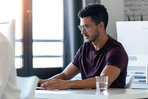 Foto de apuesto joven empresario trabajando con la computadora en la oficina.