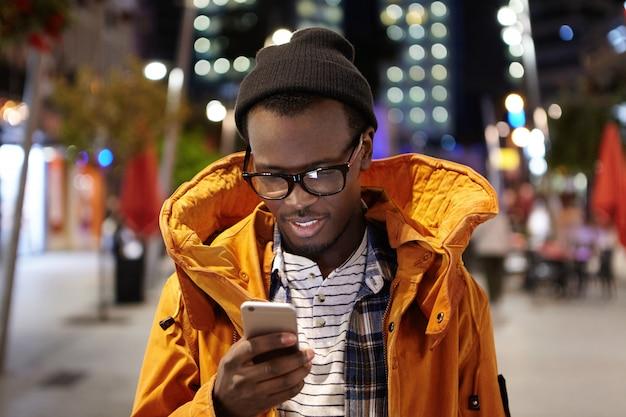 Foto de un apuesto joven estudiante afroamericano que camina por la ciudad de noche, sostiene el teléfono móvil, usa wifi urbano, navega por las imágenes en las redes sociales. tecnología moderna y comunicación