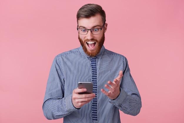 Foto de un apuesto joven con gafas, mira en el teléfono inteligente, sonríe ampliamente, feliz asombrado, aislado en un fondo rosa.