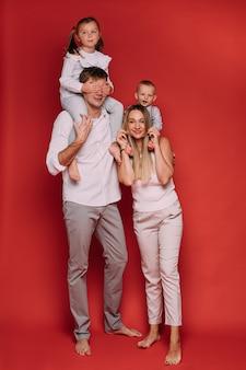 Foto de archivo de cuerpo entero de amoroso padre y madre con hijos sobre los hombros posando sobre fondo rojo. hija cerrando los ojos del padre con las manos.