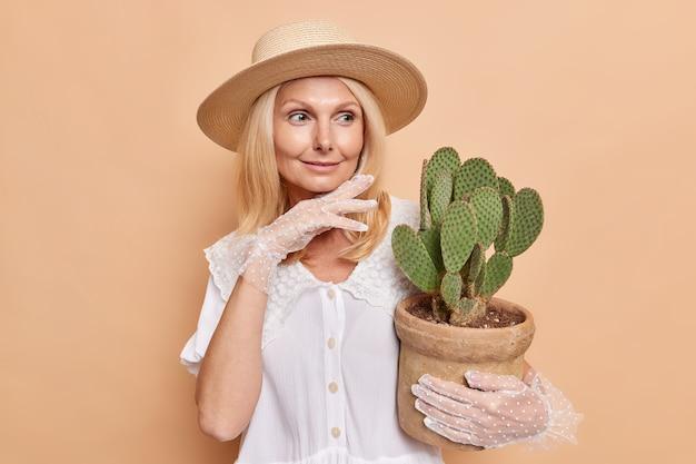 La foto de la aristocrática dama de mediana edad usa sombrero, blusa blanca y guantes de encaje, toca la barbilla, mira suavemente a un lado, sostiene cactus en macetas, da consejos sobre cómo cuidar la planta de interior aislada en la pared beige