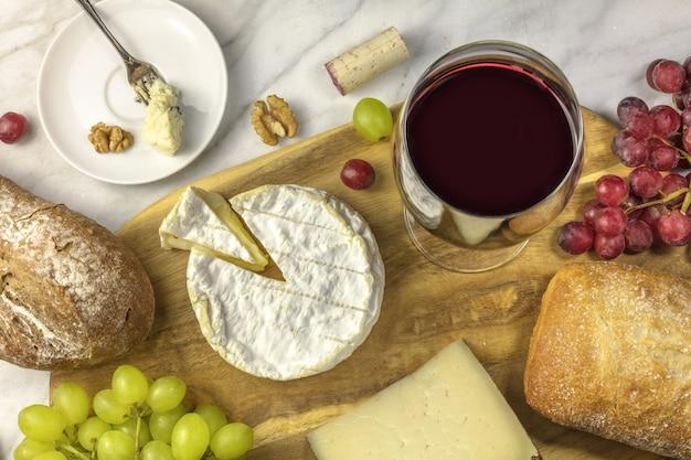 Una foto de arriba de una copa de vino tinto con queso