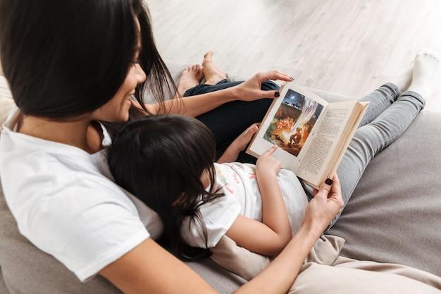 Foto de arriba de la feliz madre de familia y la niña pasando tiempo juntos, sentados en el sofá de la sala de estar y leyendo un libro