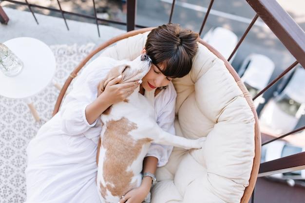 Foto desde arriba de la refinada dama de cabello oscuro y su linda mascota descansando juntos en el balcón en un cálido día de verano.