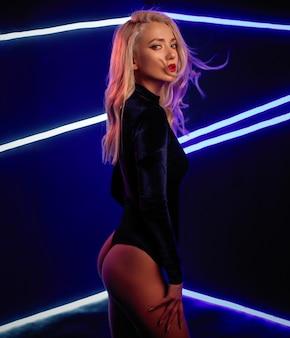 Foto de arte de moda de modelo elegante con luz de neón en el fondo.