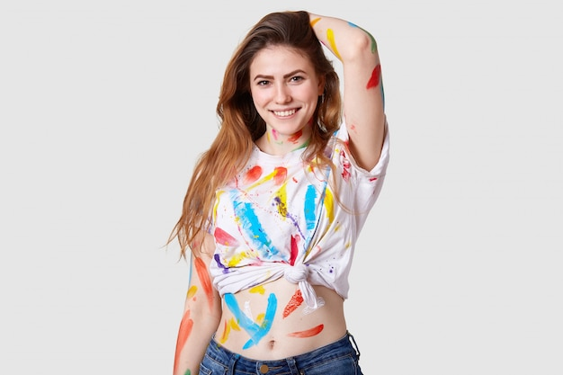 La foto de una artista femenina feliz y encantada trabaja en un proyecto de arte, sonríe positivamente, se siente inspirada y contenta, tiene la parte superior y la mano sucias con pinturas de colores, aisladas sobre una pared blanca