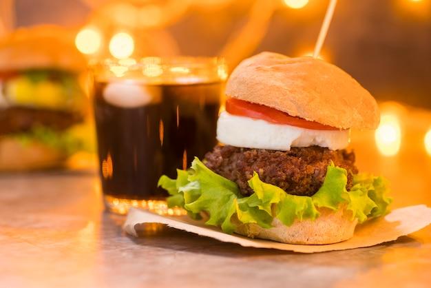 Foto artística de hamburguesa y refresco con bokeh