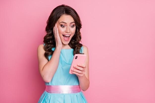 Foto de asombrada dama divertida mantenga el teléfono enviando mensajes de texto amigos leer buenas noticias aislado fondo rosa