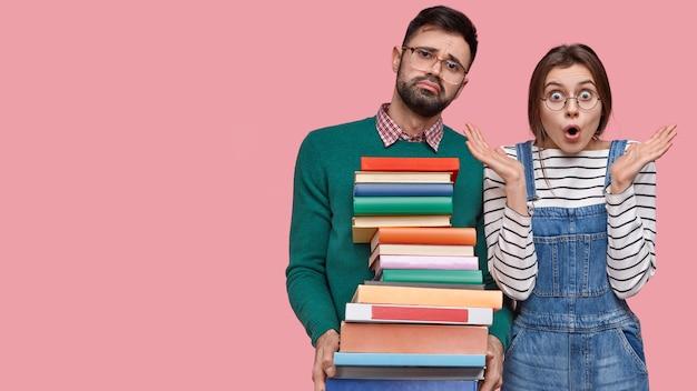 Foto de asombrada joven dama caucásica en overoles de mezclilla, hombre sin afeitar cansado lleva libros de texto