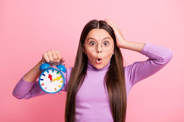 Foto de asombrado niño pequeño niña mantenga el reloj toque la cabeza de la mano aislada sobre fondo de color pastel