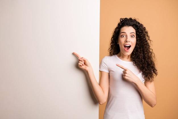 Foto de asombrosa dama emocionada que indica el dedo en la pancarta de descuento vacía gran cartel blanco use ropa casual blanca aislada de fondo de color beige pastel