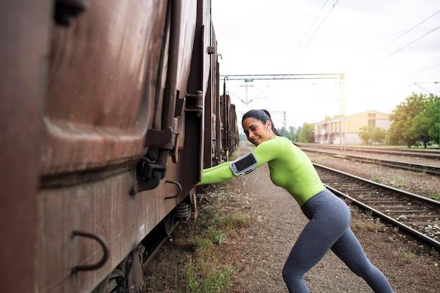 Foto de atleta femenina estirando su cuerpo después de correr en la estación de tren de la ciudad.