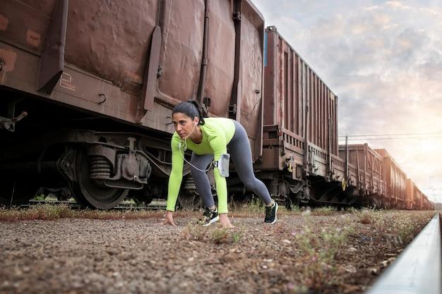 Foto de un atleta preparándose para correr por los trenes en la estación.