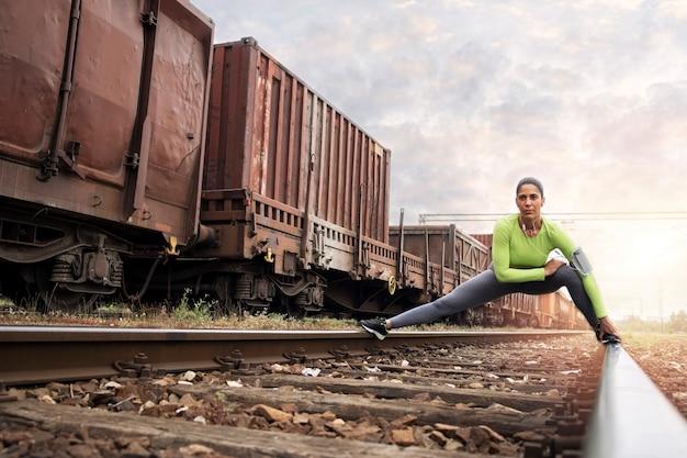 Foto de un atleta en ropa deportiva estirando su cuerpo en el ferrocarril y preparándose para correr.