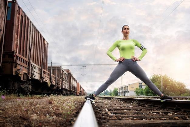 Foto de un atleta en ropa deportiva de pie en el ferrocarril y preparándose para correr.