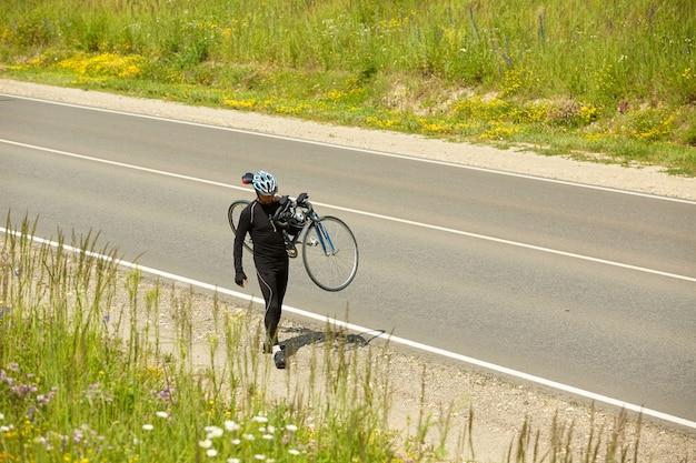 Foto de un atleta de triatlón llevando su bicicleta en una carretera abierta