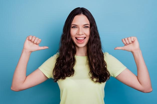 Foto de la atractiva chica alegre y segura de sí misma con los pulgares directos a sí misma alardeando sobre fondo azul.