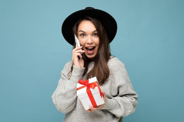 Foto de atractiva feliz positiva sorprendida joven morena aislada sobre fondo azul pared vistiendo sombrero negro y suéter gris con caja de regalo hablando por teléfono móvil y mirando a cámara.