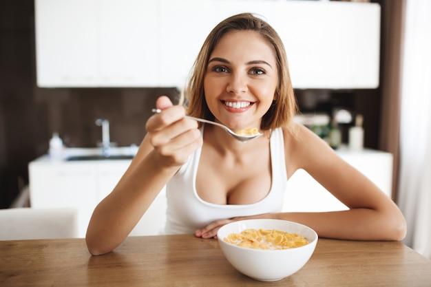 Foto de atractiva jovencita comiendo copos de maíz con leche en la cocina sonriendo