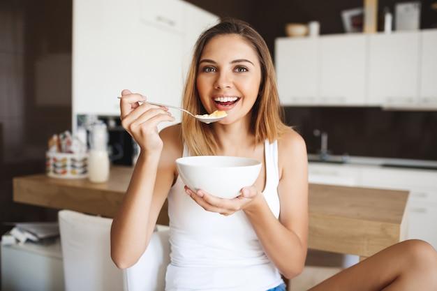 Foto de atractiva jovencita comiendo copos de maíz con leche en la cocina