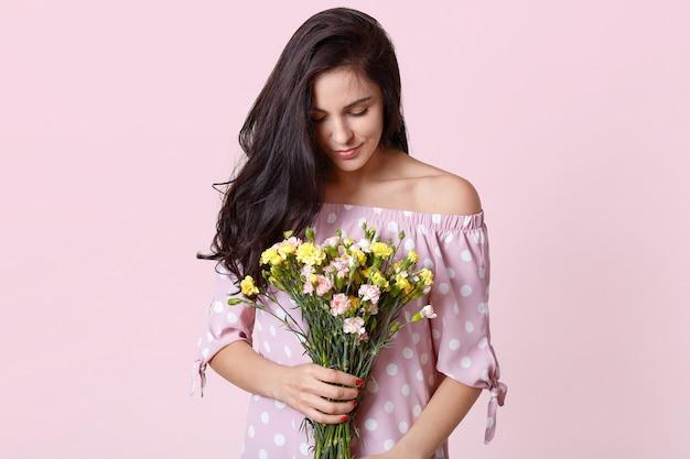 La foto de la atractiva modelo femenina morena tiene flores de primavera, usa un vestido de lunares