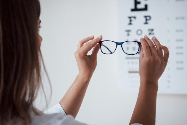 Foto de atrás. mujer mirando a través de la tabla optométrica de gafas.