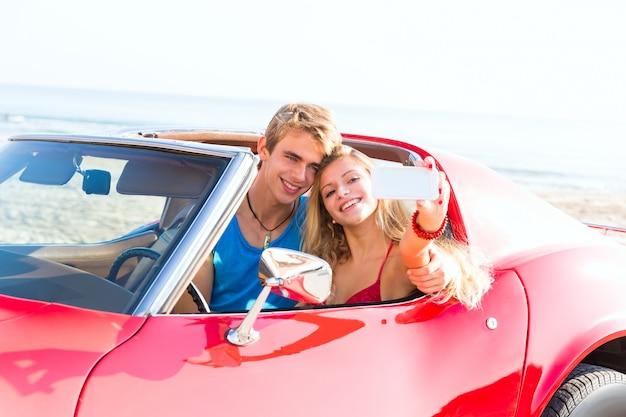 Foto autofoto de joven pareja adolescente en convertible.
