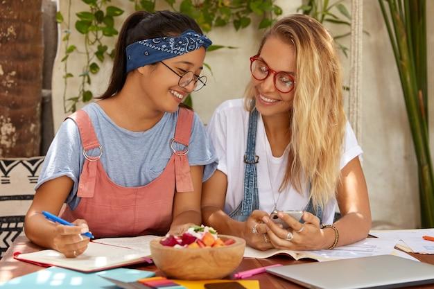 Foto de autónomos felices sentarse en el escritorio, escribir registros en el organizador, realizar pagos en el teléfono móvil