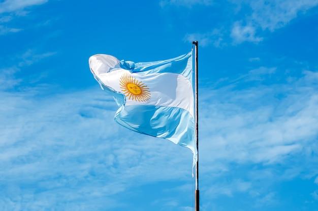 Foto de la bandera de argentina contra un cielo azul con nubes