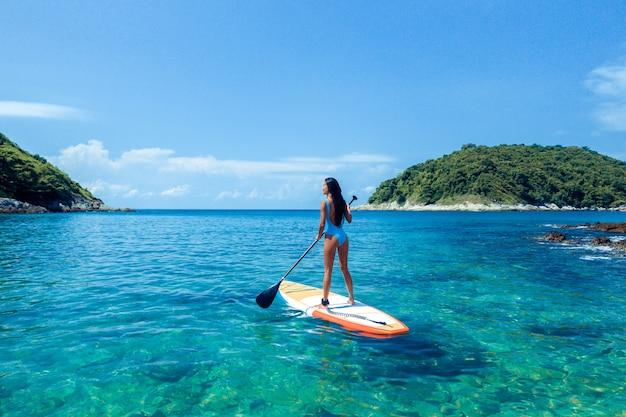 Foto de una bella morena posando de pie en un kayak