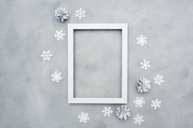 Foto blanco marco de navidad con copyspace. vacaciones . copos de nieve y conos