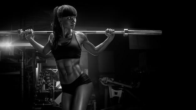 Foto en blanco y negro de mujer joven en forma en gran forma de elevación