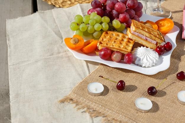 Foto de bodegón y comida un plato con frutas y gofres se encuentra en una arpillera