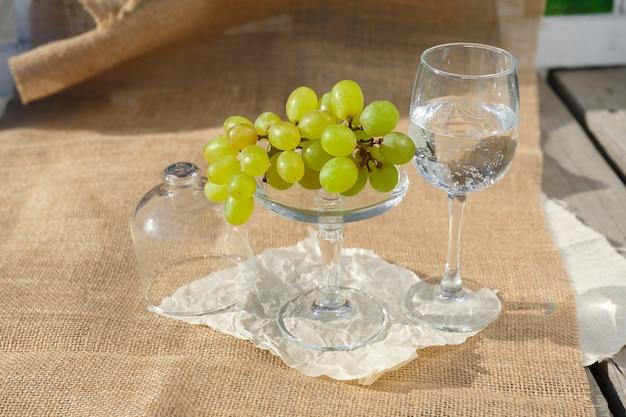 Foto de bodegón y comida un plato con un racimo de uvas se encuentra en una arpillera