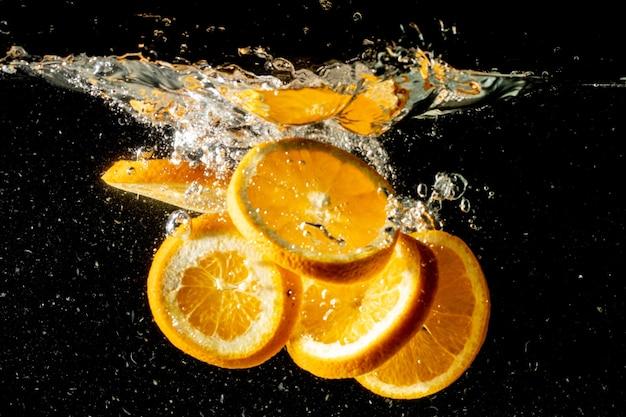 Foto de bodegón de rodajas de naranja cayendo bajo el agua y haciendo un gran chapoteo