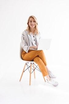 Foto de bonita mujer europea vistiendo ropa casual sonriendo y usando la computadora portátil mientras está sentado en una silla aislada sobre la pared blanca