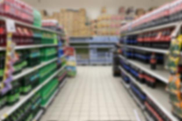 Foto borrosa de agua con gas en el estante en el supermercado.