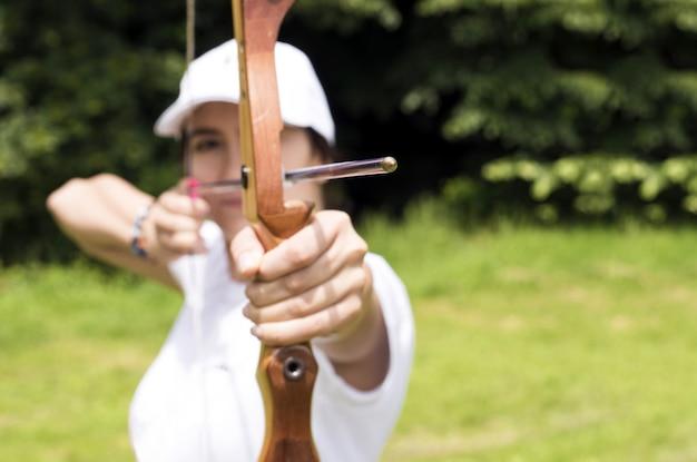 Foto borrosa de una arquera sosteniendo un arco de madera y apuntando al objetivo
