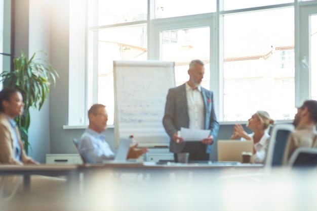 Foto borrosa de una gente de negocios que tiene una reunión en la oficina moderna trabajando juntos