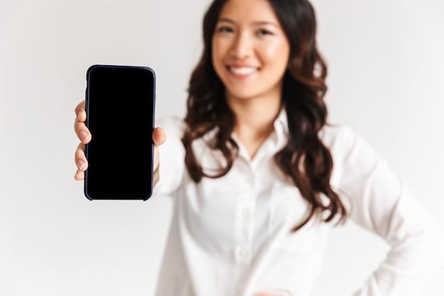 Foto borrosa de mujer asiática sonriente con el pelo largo y oscuro de pie y mostrando smartphone