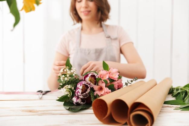 Foto borrosa de mujer joven floristería recogiendo ramo de flores diferentes, sobre la mesa en el taller