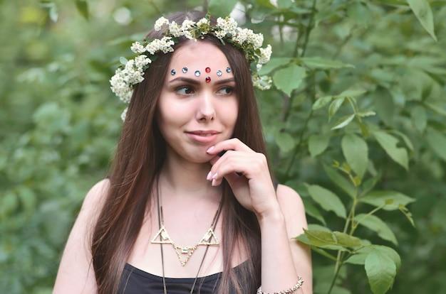 Una foto del bosque de una hermosa joven morena de complementos europeos.
