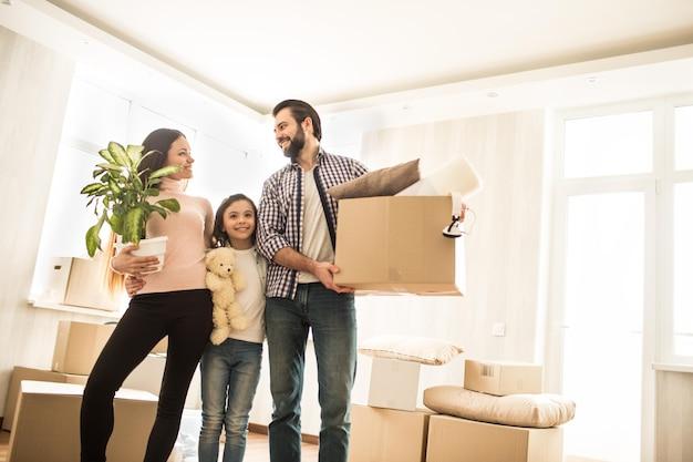 Una foto de una buena familia de pie juntos en la habitación. los padres se miran y sonríen. el hombre sostiene una caja en sus manos mientras la mujer tiene una planta. hay una niña pequeña entre ellos
