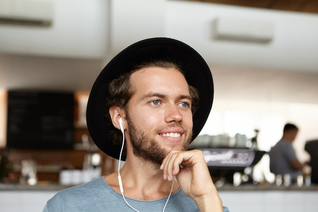 Foto de cabeza de apuesto joven estudiante barbudo con sombrero negro sonriendo con alegría, escuchando música con auriculares
