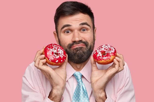 Foto de cabeza de un atractivo hombre barbudo con cabello negro, tiene una expresión amistosa, sostiene deliciosas donas rojas, vestido con ropa formal, modelos sobre fondo rosa