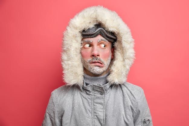 Foto de cabeza de un hombre emocionado y desconcertado que frunce los labios y mira a un lado, tiembla por las bajas temperaturas y necesita abrigarse, viste una chaqueta gris con capucha de piel.